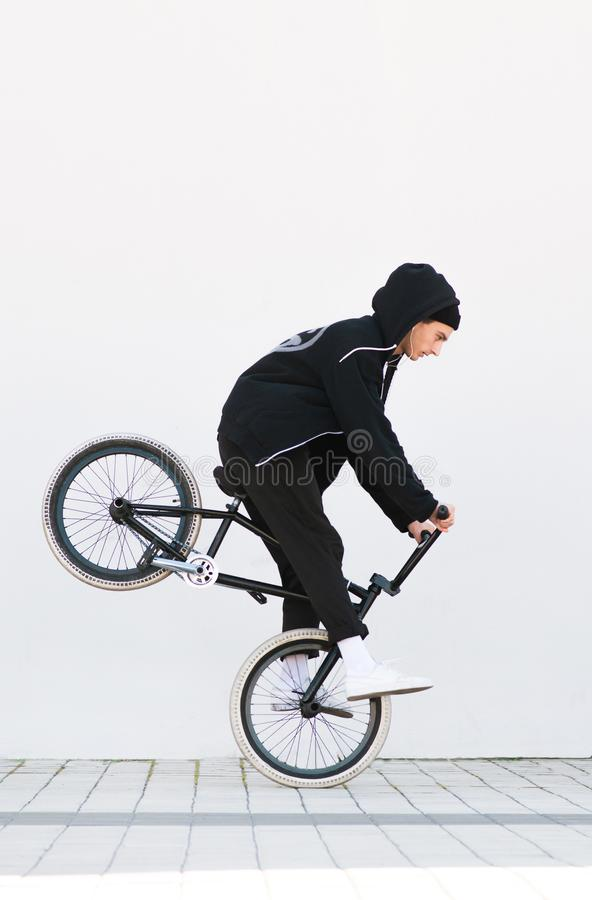 Racer makes a trick in against the background of a white wall. Bmx rider with a bicycle in flight on a white background stock photo