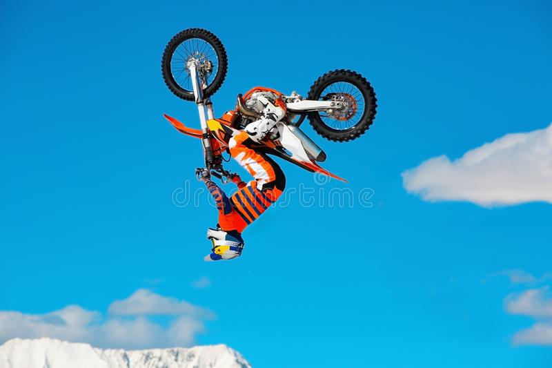 Racer on motorcycle participates in motocross cross-country in flight, jumps and takes off on springboard against sky royalty free stock photo