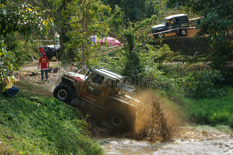 Racer offroad at terrain racing car competition. DAMBRI, VIET NAM- FEB 23: Racer offroad at terrain racing car competition, motor wade cross lake, splash mud royalty free stock photography