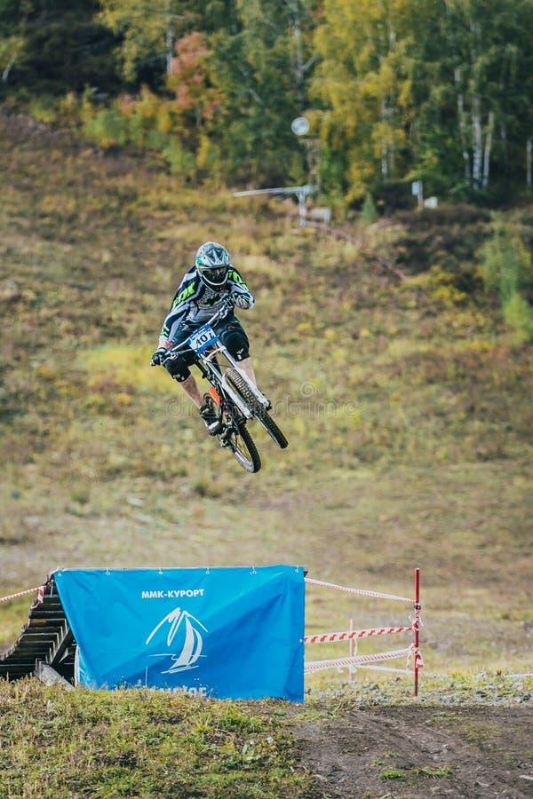 Racerbil på berget som cyklar hopp från en språngbräda arkivbilder