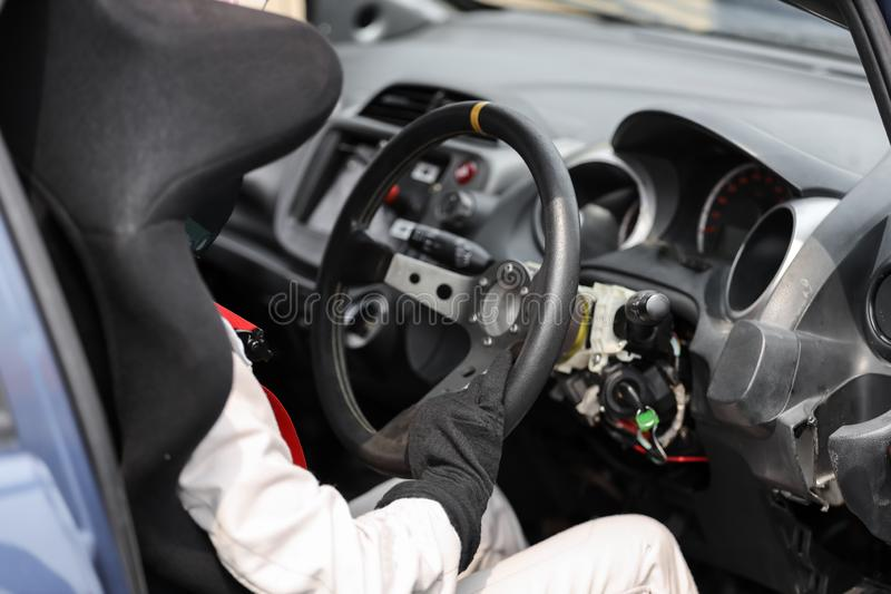 Racerbilsförare som bär skyddande läder, och hjälm som rymmer ett styrhjul royaltyfri bild