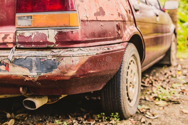 Rachado e descascando a pintura em um carro velho no parque fotografia de stock