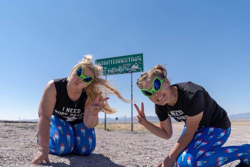 RACHEL, NV: Δύο ενήλικες γυναίκες θέτουν μπροστά από το εξωγήινο σημάδι εθνικών οδών κατά μήκος του SR 375 στη Νεβάδα στοκ φωτογραφίες με δικαίωμα ελεύθερης χρήσης