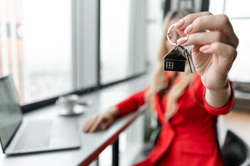 100 rachunków pojęcia dolara dom robić hipotekuje robić Kobieta w czerwonego korala garnituru mienia kluczu z domem kształtował k obrazy royalty free