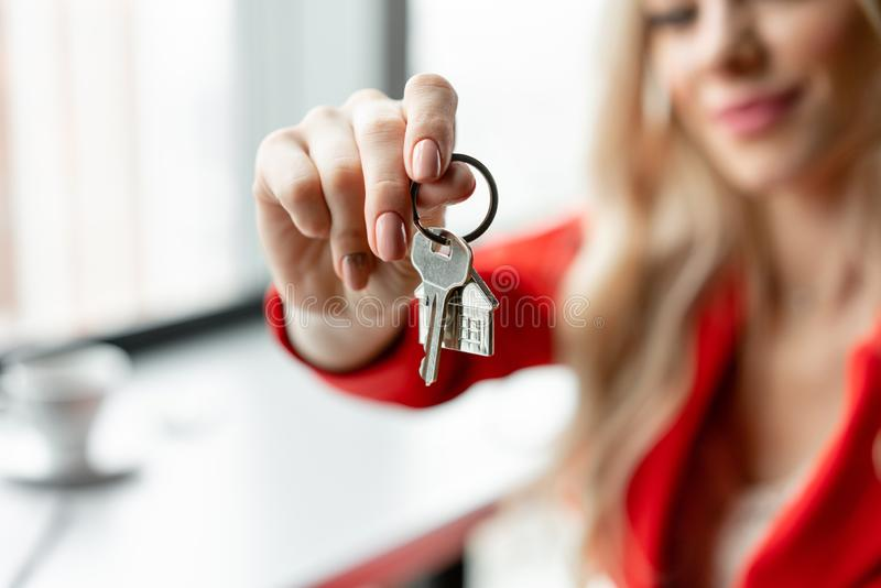 100 rachunków pojęcia dolara dom robić hipotekuje robić Kobieta w czerwonego korala garnituru mienia kluczu z domem kształtował k zdjęcie stock