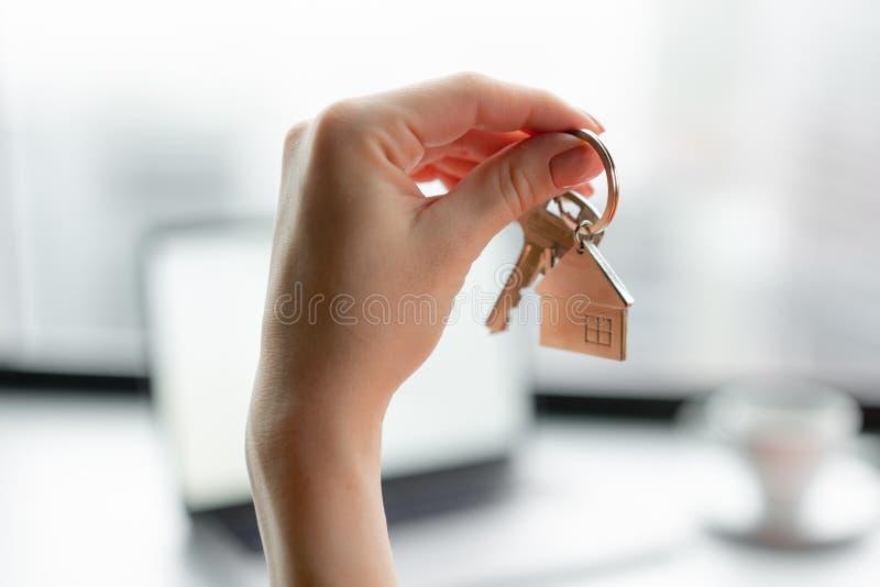 100 rachunków pojęcia dolara dom robić hipotekuje robić Kobieta w czerwonego korala garnituru mienia kluczu z domem kształtował k obraz stock
