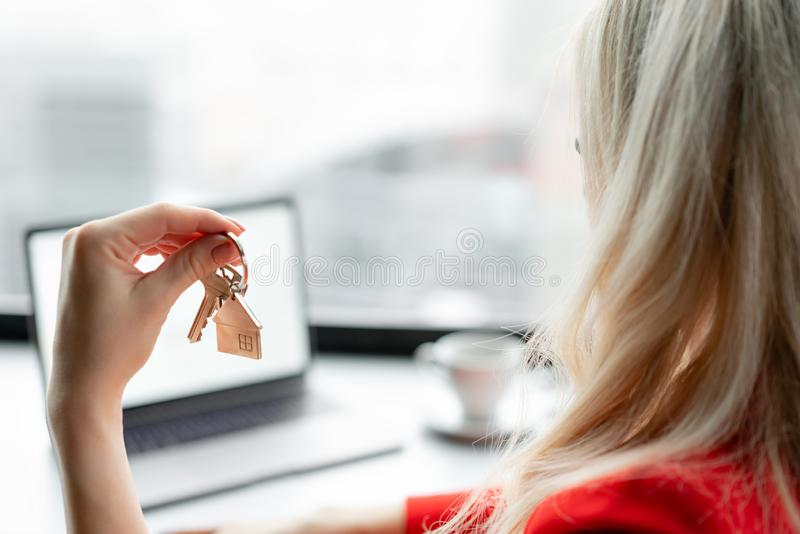 100 rachunków pojęcia dolara dom robić hipotekuje robić Kobieta w czerwonego korala garnituru mienia kluczu z domem kształtował k fotografia stock