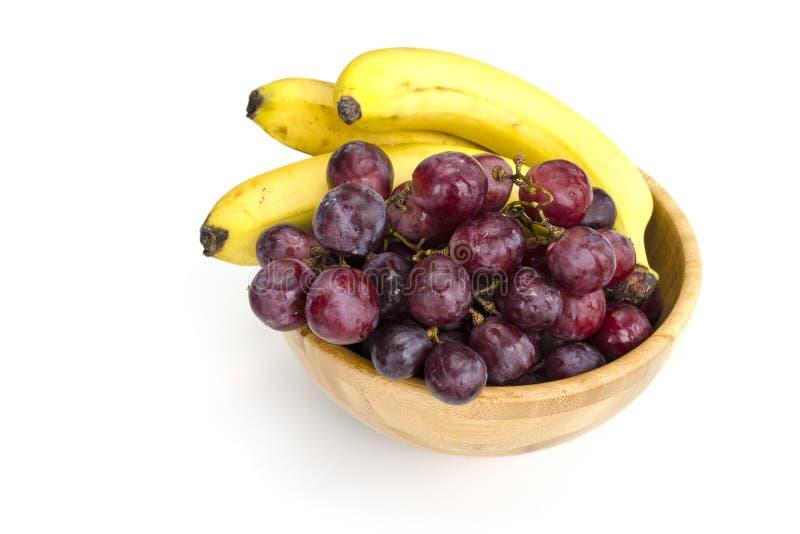 Racimos jugosos aislados de uvas rojas grandes y de plátanos maduros en un cuenco de madera imagenes de archivo