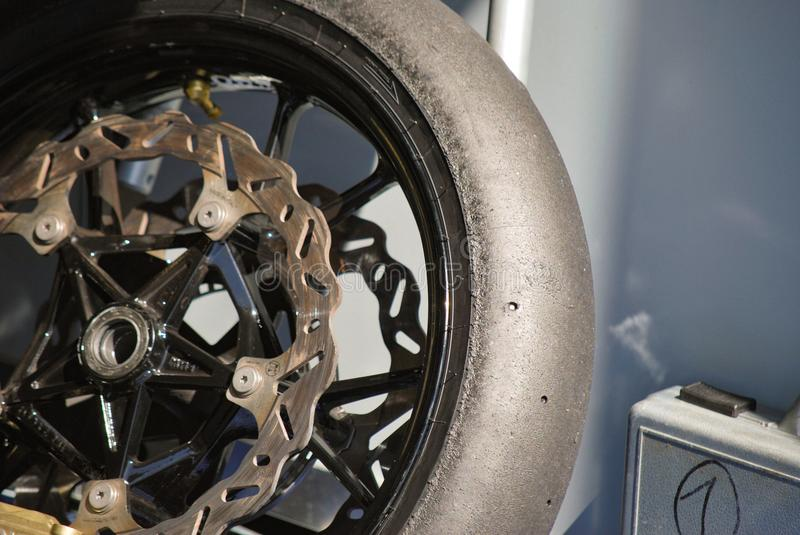 Single supersport bike wheel with driven slick tire. Racing bike`s driven slick tyre on black rim with breaking discs in box at racetrack. endurance 24h race royalty free stock images