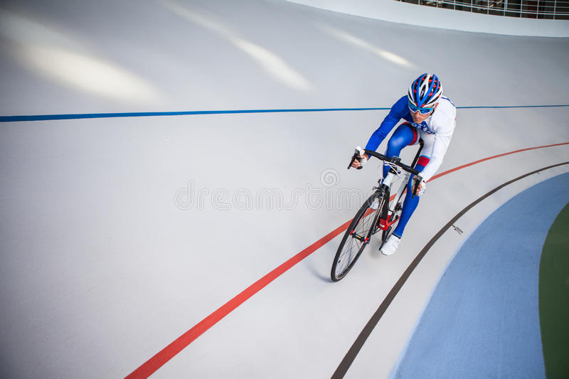 Racing cyclist on velodrome outdoor. stock image