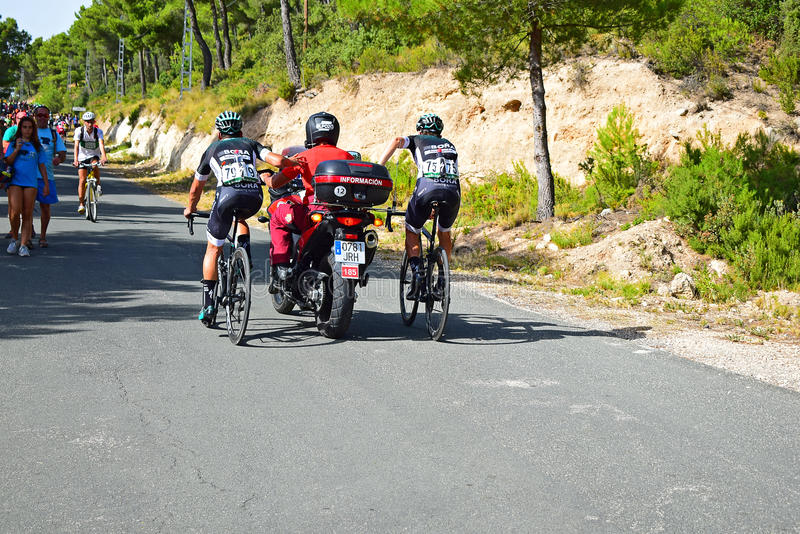 Racing Cyclists Holding Onto Motorcycle La Vuelta España. Bora Hansgrohe riders hitch a ride up the hill at the end of stage eight Xorret De Cati in the 2017 stock photos