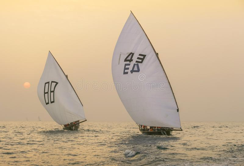Racing Dhows at Sunset. DUBAI, UAE - December 16, 2004: Traditional racing dhows approaching the finishing line off Dubai at sunset stock image