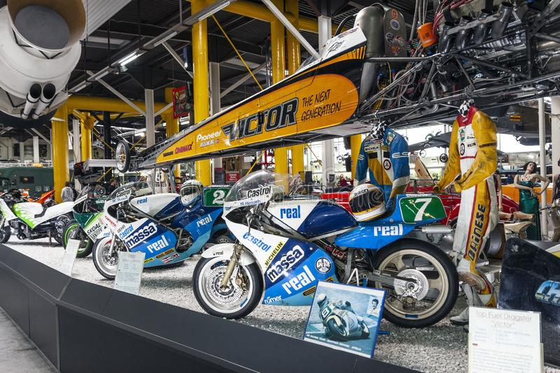 Racing motorbikes and sport equipment on display in automotive museum royalty free stock photography