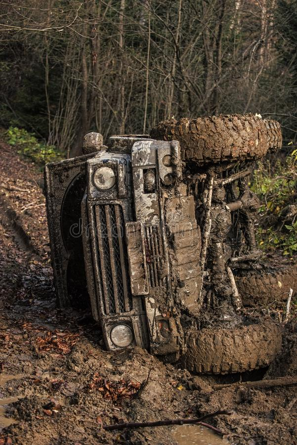Racing on off-road cars. Dirty offroad car with dark forest on background. SUV rolled over on path covered with leaves. Crossover in dangerous situation royalty free stock photography