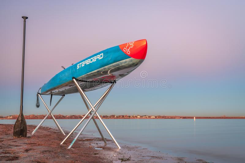 Racing stand up paddleboard on stands. Loveland, CO, USA - November 20, 1918: Dusk over a lake after paddling - a racing stand up paddleboard by Starboard on stock images