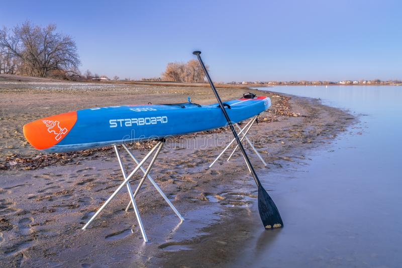 Racing stand up paddleboard on stands. Loveland, CO, USA - November 20, 1918: Dusk over a lake after paddling - a racing stand up paddleboard by Starboard on royalty free stock photos