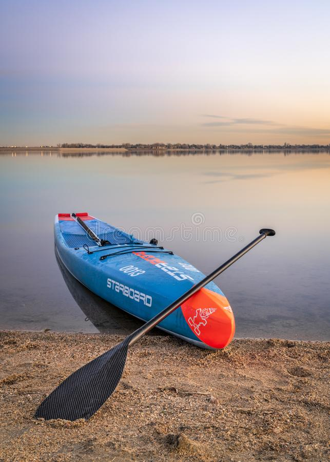 Racing stand up paddleboard on stands. Loveland, CO, USA - November 26, 1918: Dusk over a lake after paddling - a racing stand up paddleboard by Starboard with a stock image