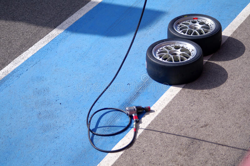 Racing tires. And pneumatic wrench for a pit stop stock photography