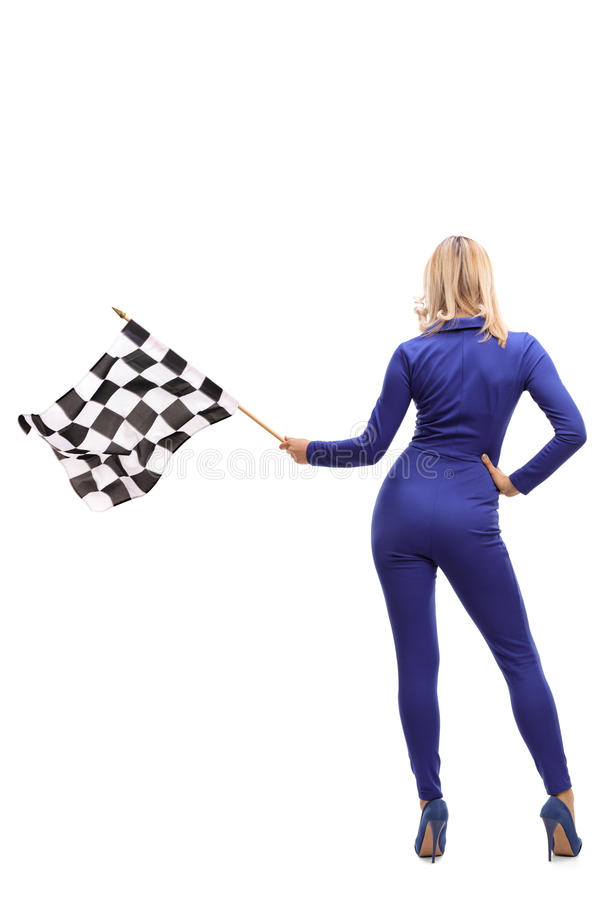 Racing woman waving a checkered race flag. Full length rear view studio shot of a racing woman waving a checkered race flag isolated on white background stock image