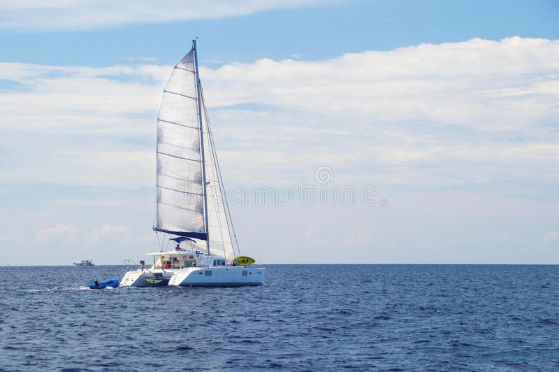 Racing yacht in the sea. On blue sky background royalty free stock images