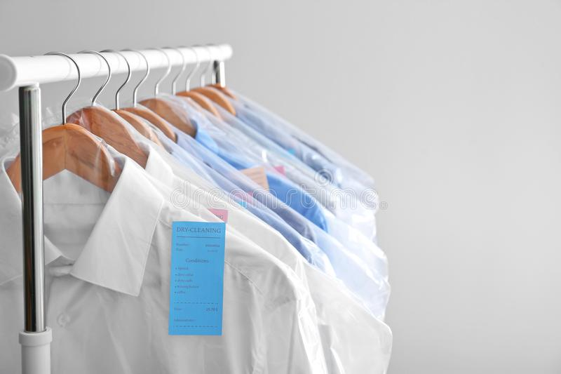 Rack with clean clothes on hangers after dry-cleaning. Against light background stock images