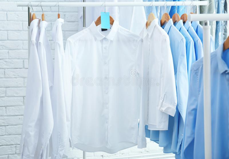 Rack with clean clothes on hangers after dry-cleaning. Indoors royalty free stock images