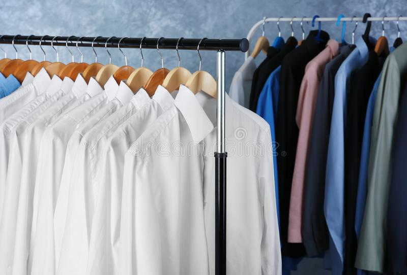 Rack of clean clothes hanging on hangers. At dry-cleaning royalty free stock photo