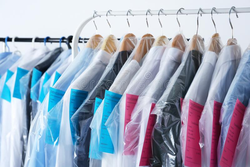 Rack of clean clothes hanging on hangers. At dry-cleaning royalty free stock images