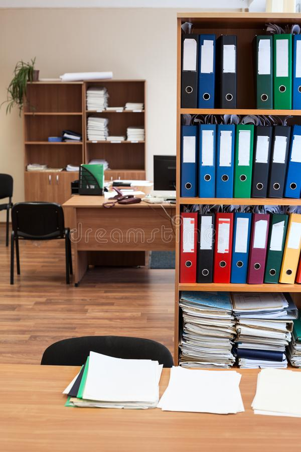 Rack with color paper folders is in an empty office room, nobody stock photos