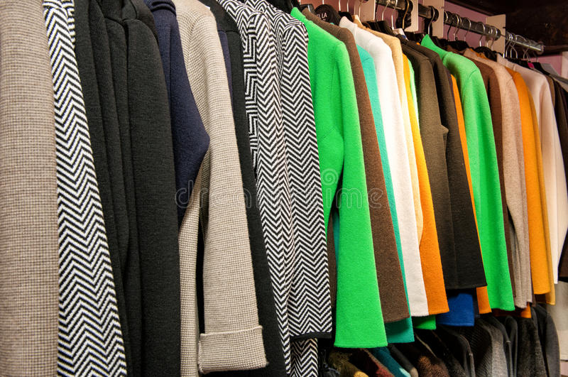 Rack of Colorful Garments Hanging on Rod. Rack of Garments Hanging in a Row - Colorful Shirts and Jackets in Variety of Patterns and Styles Hanging from Rack in royalty free stock photo