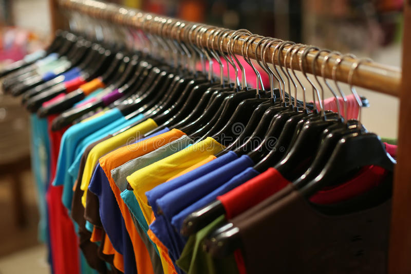 A rack of colorful shirts hanged for sale at a fair royalty free stock photography
