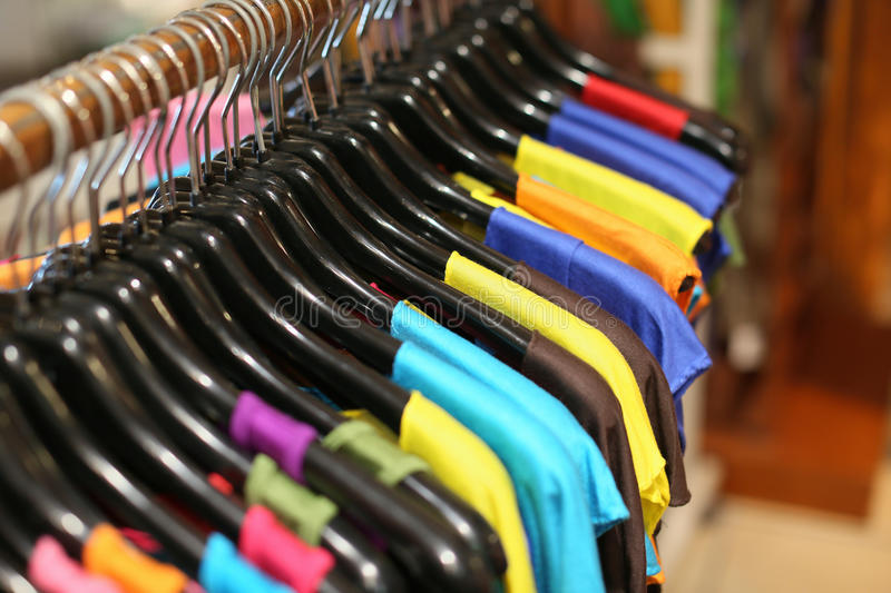 A rack of colorful shirts hanged for sale at a fair stock photos