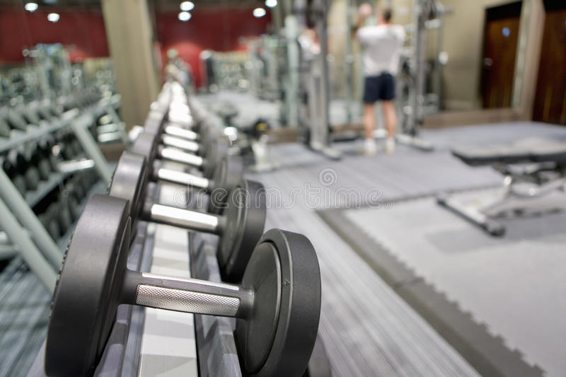 Rack of dumbbells in health club with man lifting weights in background stock images