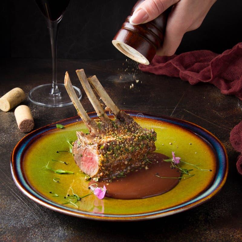 Rack of lamb in breaded pistachio nuts, dark sauce and herbs, pink meat, medium roast. Beautiful restaurant serving stock photo