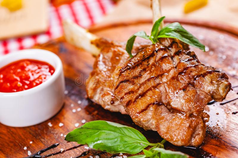Rack of lamb fried with aromatic olive oil, herbs and spices on wooden board. Close up stock photos