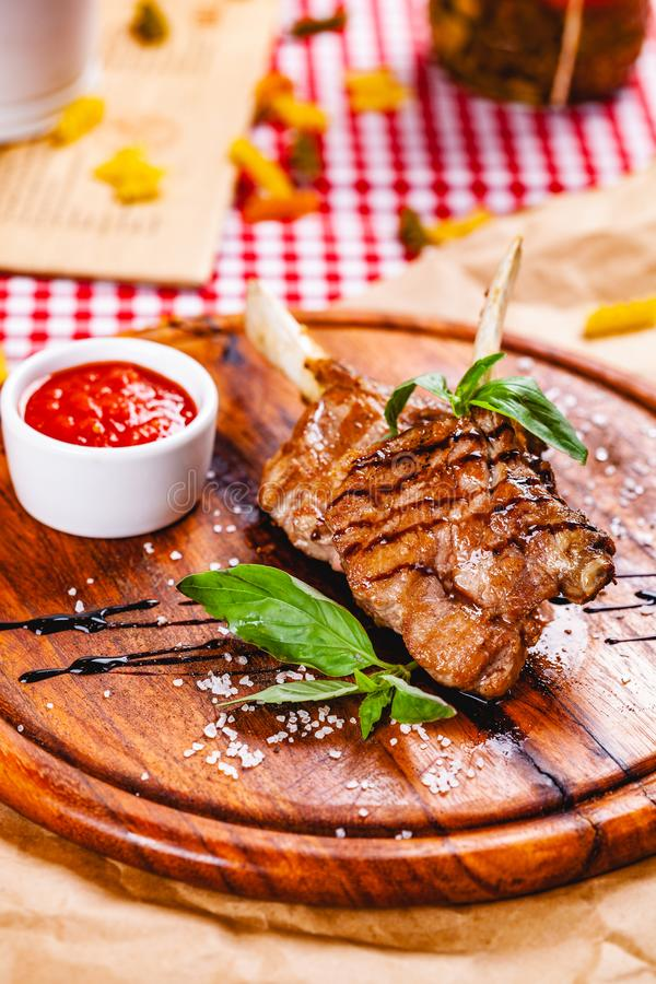 Rack of lamb fried with aromatic olive oil, herbs and spices on wooden board. Close up royalty free stock photography