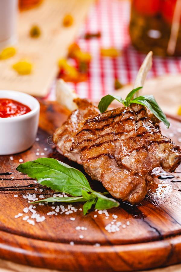 Rack of lamb fried with aromatic olive oil, herbs and spices on wooden board. Close up stock photography