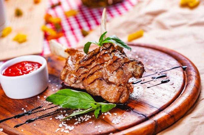Rack of lamb fried with aromatic olive oil, herbs and spices on wooden board. Close up royalty free stock photo