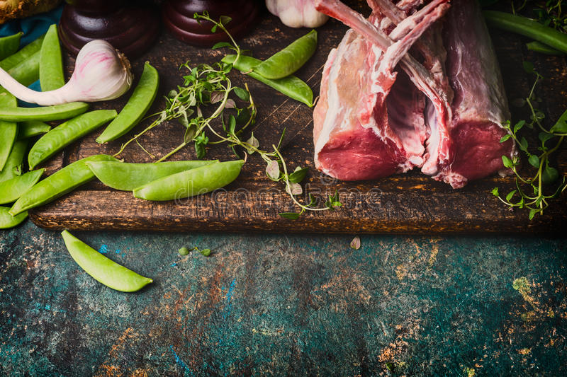 Rack of lamb with green pea pods, cooking preparation on rustic background, top view. Border stock photography