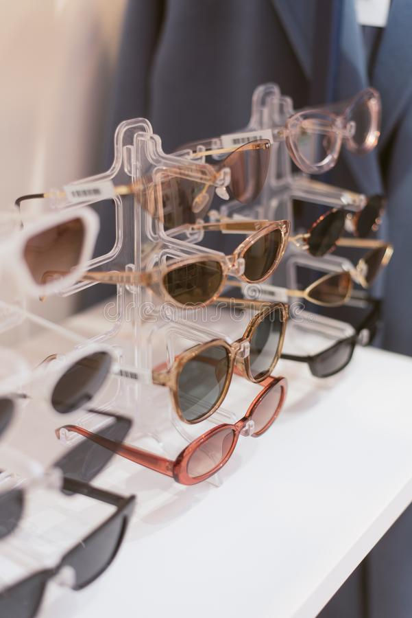 Rack with stylish trendy plastic glasses. Retail sale of stylish glasses royalty free stock photos
