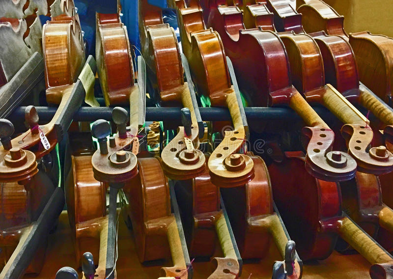 Rack of violins awaiting work in violin repair shop. Rack of various styles of violins awaiting restoration or repair work in violin repair shop. Luthier`s stock images