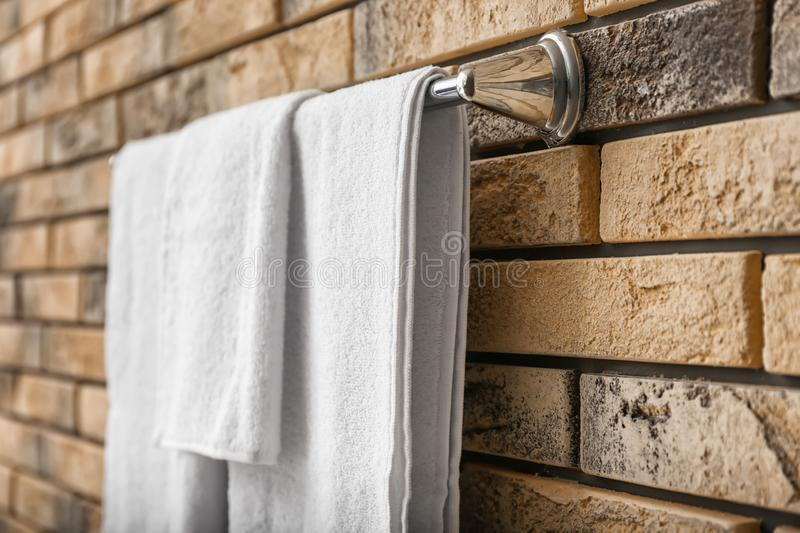 Rack with white terry towels on brick wall, closeup stock photo