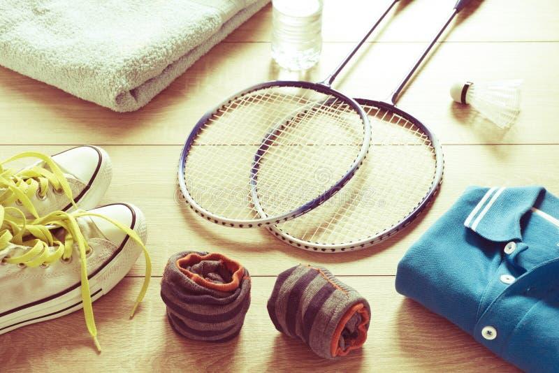 Racket för badminton, fjäderboll, poloskjortor, skor, handduk och vatten på ett trägolv royaltyfri foto