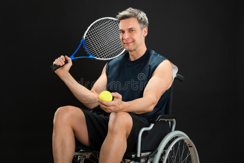 Racket och boll för rörelsehindrad man hållande arkivbild