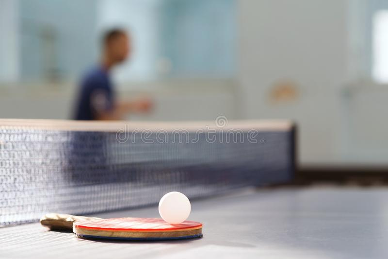 A racket with a white ball lies on a tennis table on the background of a tennis net and an athlete in the gym.  stock photography