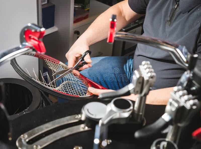 Racketfrilansreporter som väver arga rader av syntetisk katgut i en tennisracket på a arkivfoton