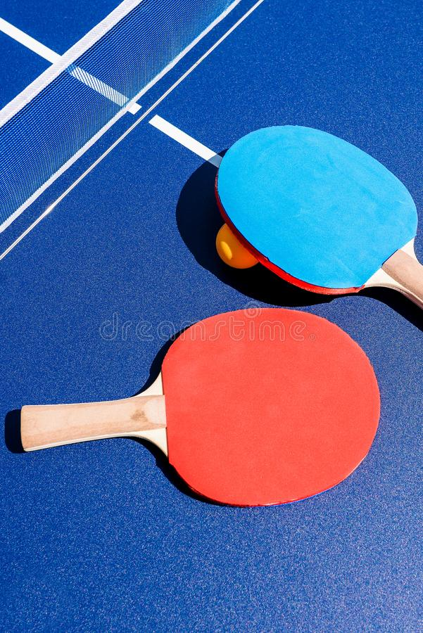 Rackets on the table tennis and orange ball. Ping pong and table tennis. Sports and outdoor activities. Healthy lifestyle. Banner. In a sports facility or stock photography