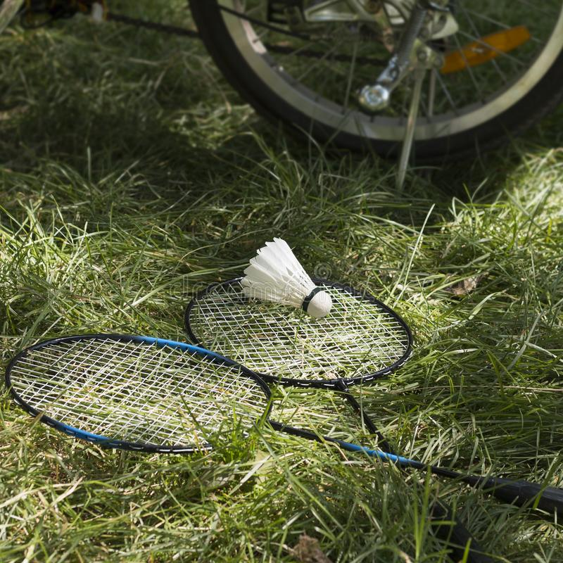 Rackets with white shuttlecock on green grass and wheel of electric bicycle on the background. Sunny day. Square image, selective focus royalty free stock photo
