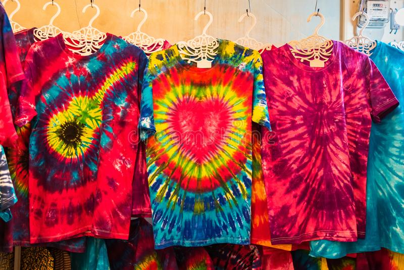 Racks of tie-dyed clothing for sale at an outdoor marke.Phuket.Thailand stock image