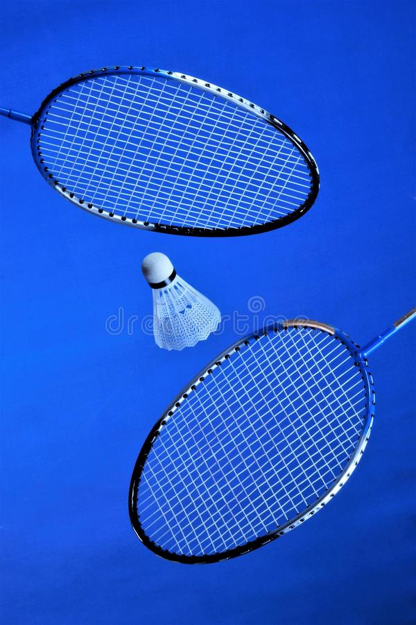 Racquets and a flying shuttlecock for badminton. Players rivals summer recreation, spectacular and affordable, is an Olympic sport. That develops agility, speed royalty free stock photo